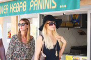 Newly single sisters Paris and Nicky Hilton shopping in the streets of St Tropez as a large crowd of admirers follows. Paris and Nicky attended the concert Snoop Dogg put on in the VIP room at Club 55 in St Tropez. Paris was seen stopping to buy a roasted chicken before returning to the hotel.