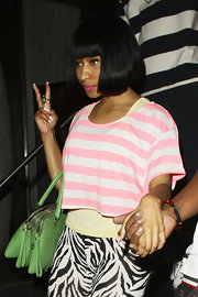 Nicki Minaj added an unexpected pop of color to her funky dinner attire with a lime green three-zip Lily Twist satchel.