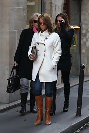Julianne Hough toured Paris wearing knee high leather cognac boots. She paired the au courant footwear with jeans and a classic winter white coat.