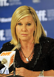 Olivia Newton-John wore a large pearl pendant necklace at a press conference.