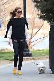 Olivia Palermo chose a pair of cool skinny jeans, which featured a double row of zipper pockets on each side, for her look while out walking her dog.