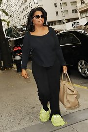 Oprah Winfrey was comfy in a fitted black blouse, slacks, and slippers while shopping in New York City.