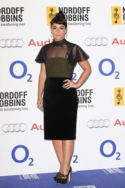 Jessie Ware showed off her unique style with this olive green dress that featured a black pencil skirt and a sheer dotted over lay at the bodice and sleeves.