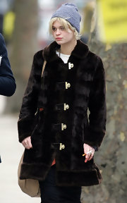 Pixie wears an A-line fur coat with unique toggle buttons.