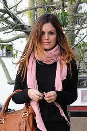 Rachel wore a feminine blush pink scarf over a black sweater. This light-colored accessory added a sweet spring finish to her casual look.