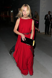 The frail fashionista carried a black patent leather envelope clutch with a contrasting yellow interior. This chic handbag complemented the belted detailing on Rachel's flowing red gown.