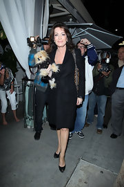Lisa dons a black wool coat while carrying her puppy out in Beverly Hills.