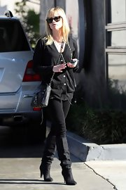 Going for an all black look, Reese wore a pair of suede knee-high boots. We usually see Reese in bright cheery colors, so it's nice to see an edger side of her.