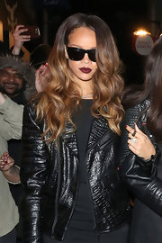 Rihanna showed her edge with a black snakeskin leather jacket and deep berry lips while out partying with friends.