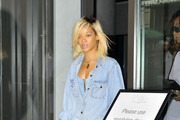 Rihanna sports all denim and a dollar sign fanny pack while leaving her New York City hotel on her way to Milk Studios.