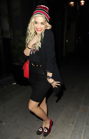 Rita posed for cameras in her red and black logo beanie while out in London.
