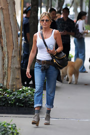 Jennifer Aniston was casual chic in loose jeans, a white tank and gray suede lace up boots.