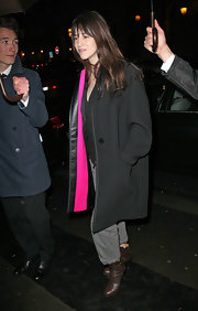 Charlotte Gainsbourg covered up in an oversize black coat with playful pink lining.