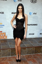 Taylor Cole teamed her daring black corset dress with matching platform pumps.