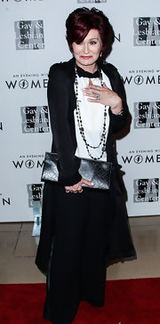 Sharon Osbourned accessorized with a patterned black leather clutch when she attended the Evening with Women gala.