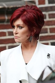 Sharon Osbourne styled her sleek black and white tailored outfit with eye-catching and abstract black gem dangle earrings.