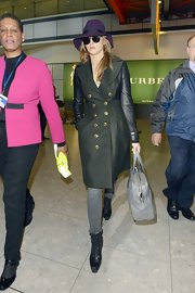 Jennifer Lawrence looked so high fashion at the airport in her purple fedora and army green coat with leather sleeves.