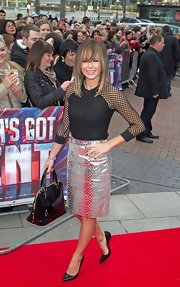 Amanda Holden carried a large black patent satchel with a bold silver zipper.