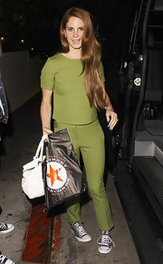 Lana Del Rey went monochromatic in split pea green pants and a matching top.