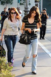 Selena looks laid back and stylish in this pair of faded torn jeans.