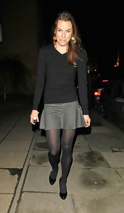 Jecca Craig wore a black V-neck sweater and short grey skirt.