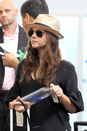 Tiffani Thiessen tried to go incognito at JFK Airport with a pair of aviators and a straw hat.