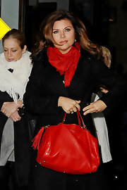 Tiffani Thiessen looked elegant on the streets of New York City in this black trenchcoat and red tasseled tote combo.