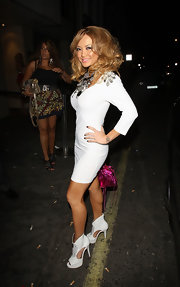 Tila went bold with a voluminous hairstyle, over the top accessories and cutout, platform Haven booties.