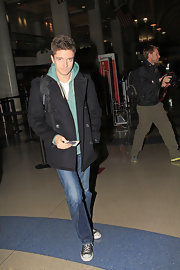 Topher Grace donned a black pea coat over a hoodie for a flight leaving LAX.