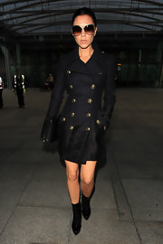 Victoria Beckham strolled through Heathrow Airport in fierce black patent high heeled boots, which she paired with a Burberry Cadet coat.