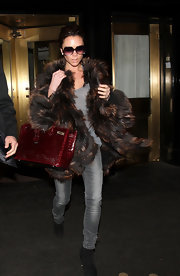 "Mrs. Beckham showed off another one of her ""Birkin"" bags. The fashionista owns enough to open up her own boutique. The crocodile printed bag added some color to her winter look."