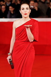 Noomi Rapace's gold cuff bracelet and red one-shoulder dress at the Rome Film Fest were a divine pairing.