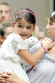A classic satin headband adds just a touch of color to Suri's white lacy look.