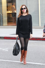 Rose McGowan added subtle contrast to her all-black ensemble with tan knee high boots. Yes, you can mix brown and black!