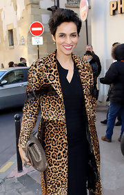 Farida Khelfa kept her look exotic with a taupe snakeskin clutch.