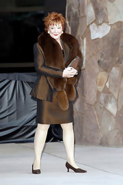 Shirley MacLaine added glam to her skirt suit with a brown fur stole.