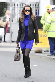 Pippa Middleton tossed on a blazer over her purple knit turtleneck dress for work.