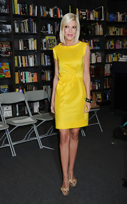 Tori wore a vibrant yellow sheath dress with a chunky bangle bracelet and patent peep toe pumps.