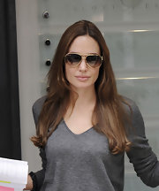 While out and about in London, Angelina Jolie kept it casual with a pair of cool aviator shades paired with soft gray sweater.