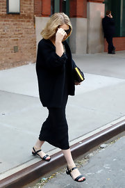 Ashley Olsen hid her face from photographers as she left her New York hotel wearing a pair of flat black casual sandals.