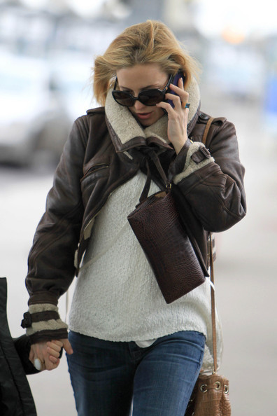 Kate Hudson made her way through Heathrow carrying a stylish brown croc-embossed wristlet.