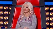Christina Aguilera momentarily cast aside her wild wardrobe in favor of a relatively demure striped dress.