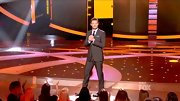 Ryan Seacrest looked as sharp as ever in a sleek dark brown slim-cut suit.